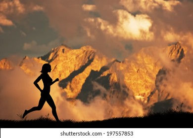 Silhouette of a woman running, jogging in the mountains scenery at sunset. Active, healthy lifestyle