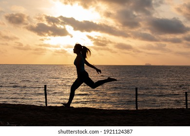 Silhouette woman running on the beach has to background the sunrise. Run towards the goal for new year concept