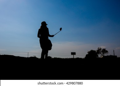 Silhouette of woman selfie. Silhouette of man posing at sunset sky background.