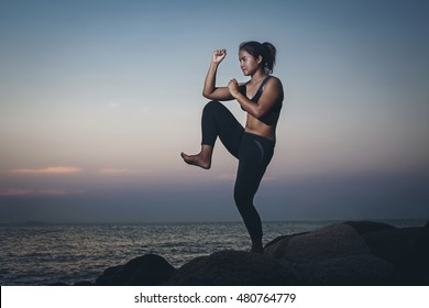 Silhouette woman. she exercise muay chaiya or thai boxing on the rock at beach, At  sunrise