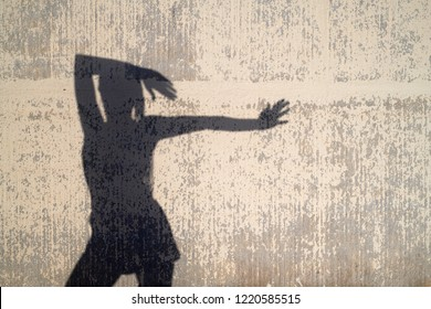 Silhouette of woman in shorts with outstretched arm in sunlight. Shade of her slim silhouette on worn-out background.