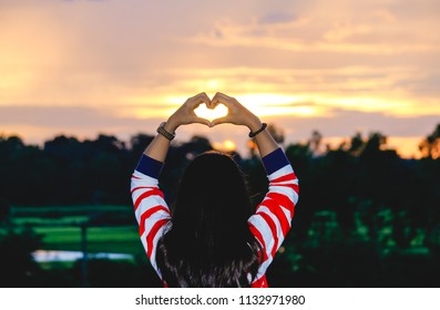 Silhouette Woman Showing Love Heart Hand Gesture in Sunrise or Sunset. Hopeful girl looking at rising sun and being in love, Love Nature Landscape concept, Winter vintage film grain filter style.