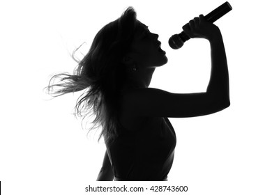 silhouette of a woman singing with a microphone in hands