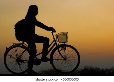 silhouette woman sit near bicycle on sunset