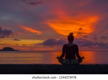 Silhouette of woman sit on the beach practice yoga at sunset