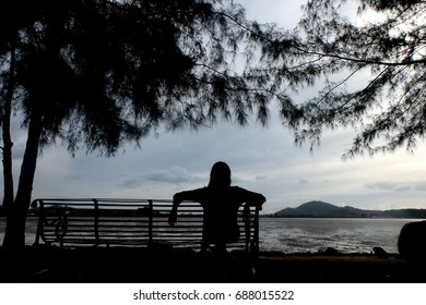 Silhouette of woman sit on the chair at beach