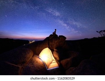 Silhouette of woman siting in yoga posture on rock formation top against dramatic dark blue red sky at sunset and bright tourist tent on huge boulder under night starry sky with Milky way. Siddhasana
