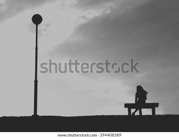 The silhouette of woman sitting alone with grey sky, concept of lonely, sad, alone, person space/  single woman on valentine