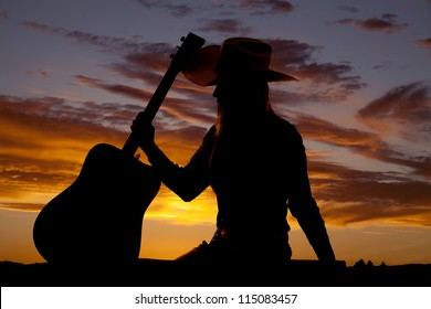 A silhouette of a woman sitting down and holding on to her guitar.