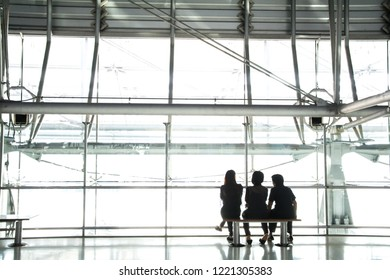 The silhouette of the woman sitting with friends by the windows of the airport with a view of the airfield with plane