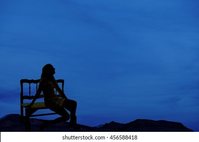 A silhouette of a woman sitting on a bench, looking up to the sky.