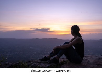 silhouette woman sitting on mountain in sunset
