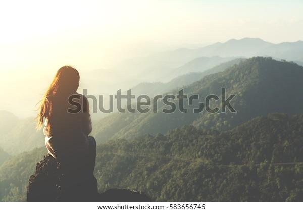 Silhouette Frau sitzend am Morgen auf dem Berg und Vintage-Filter