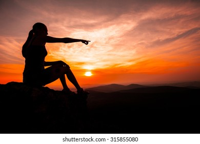 Silhouette of woman sitting on rock during the sunset meditation and pointing