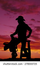 a silhouette of a woman sitting on a stool holding on to her saddle.