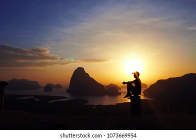 Silhouette woman sitting on the top of rock and looking at the estuary and mountains at colorful sunrise in summer. Landscape with girl, sea, mountain ridges and orange sky with sun.