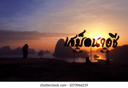 """Silhouette woman sitting on the top of rock with text """"Samet Nangshe viewpoint"""" and looking at the estuary and mountains at colorful sunrise in summer, Thailand."""