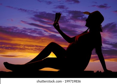 A silhouette of a woman sitting and reading a book in the outdoors.