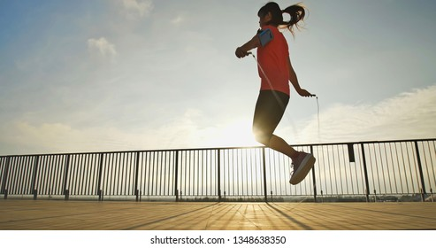 Silhouette of woman sport and rope skipping with sunset