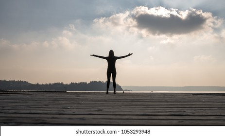 Silhouette of woman spreading arms against sky with sun behind cloud.