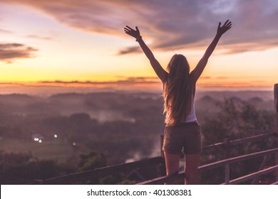 Silhouette of the woman spreading arms and standing high on the viewpoint with breathtaking view over fields in sunset light.Chocolate Hills, Bohol Island, Philippines.
