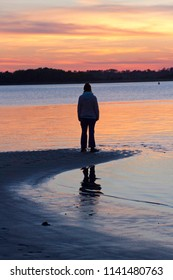 Silhouette of a woman standing alone at the water's edge of a beach at sunset enjoying nature and contemplating life