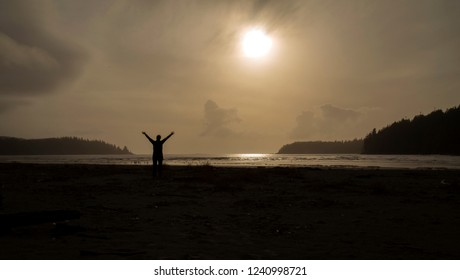 Silhouette of a woman standing at the beach with her hands stretched towards the sky.