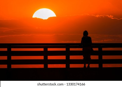 silhouette of a woman standing before the railing of a bridge land ooking to tthe sunset,cloud, shadow, black,