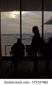 Silhouette of woman is standing beside the glass window with morning sky  at  airport with aircraft background,  Don Muaeng airport, Thailand