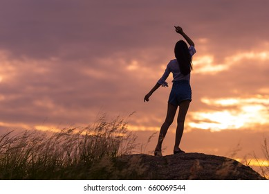 Silhouette of the woman standing  at the field  beautiful sunset on mountain