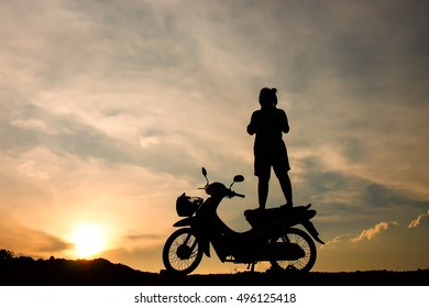 Silhouette of the woman standing on the motorcycles couple in sunset
