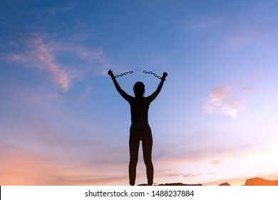 silhouette woman standing on mountain and breaking metal chains, freedom concept