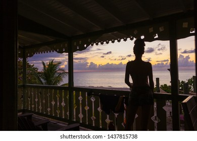 silhouette of a woman standing on the porch watch  sunset over Caribbean  sea