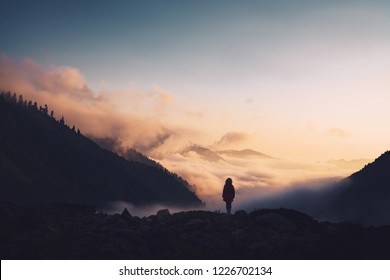Silhouette of a woman standing on a ridge, enjoying the sunset.
