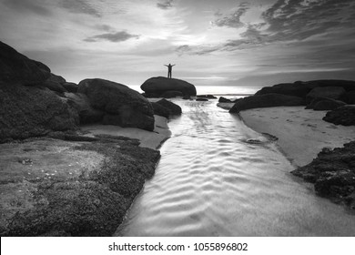 Silhouette of woman standing on a stone and spread her arms. freedom conceptual