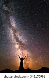 A silhouette of a woman standing on the top of the mountain next to the night sky and Milky Way galaxy with hands raised to the air