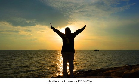 silhouette of woman standing over the horizon during sunseg