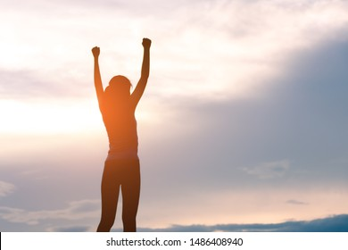 silhouette woman standing and rising hands with sun lighting, success and winner concept