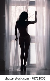 Silhouette of a woman standing at the window in the morning