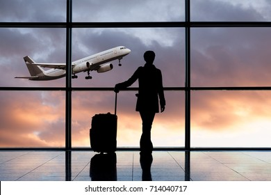 Silhouette of a woman with a suitcase standing by the window with a view of a flying plane