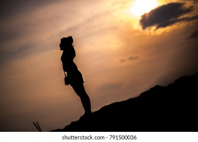 Silhouette woman in sunset.