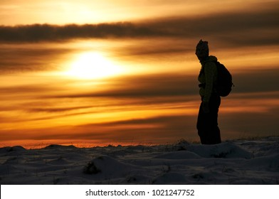 Silhouette of a woman in the sunset and a sky full of clouds.