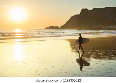 Silhouette of a woman with surfboard walking on the beach at sunset. Algarve, Portugal