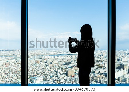 Silhouette of woman taking photo on Tokyo city