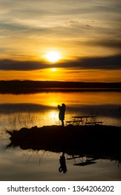 Silhouette of woman taking photo of sunset with mobile phone, reflection in water.