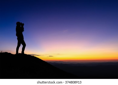 silhouette of woman taking photograph on the top of mountain and enjoy colourful sky