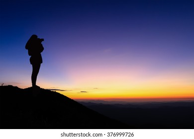 Silhouette of woman taking photograph on the top of mountain and enjoy colourful sky.