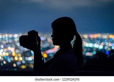 silhouette woman taking picture with dslr camera at night in thailand.