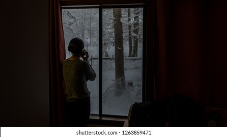 Silhouette of woman talking on phone at window looking out at snow