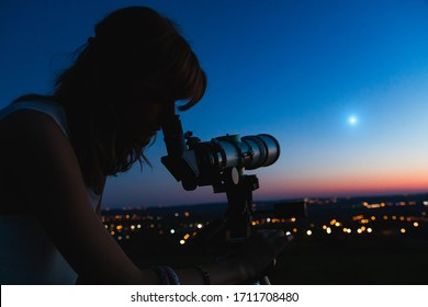 Silhouette of a woman and telescope with twilight sky.
